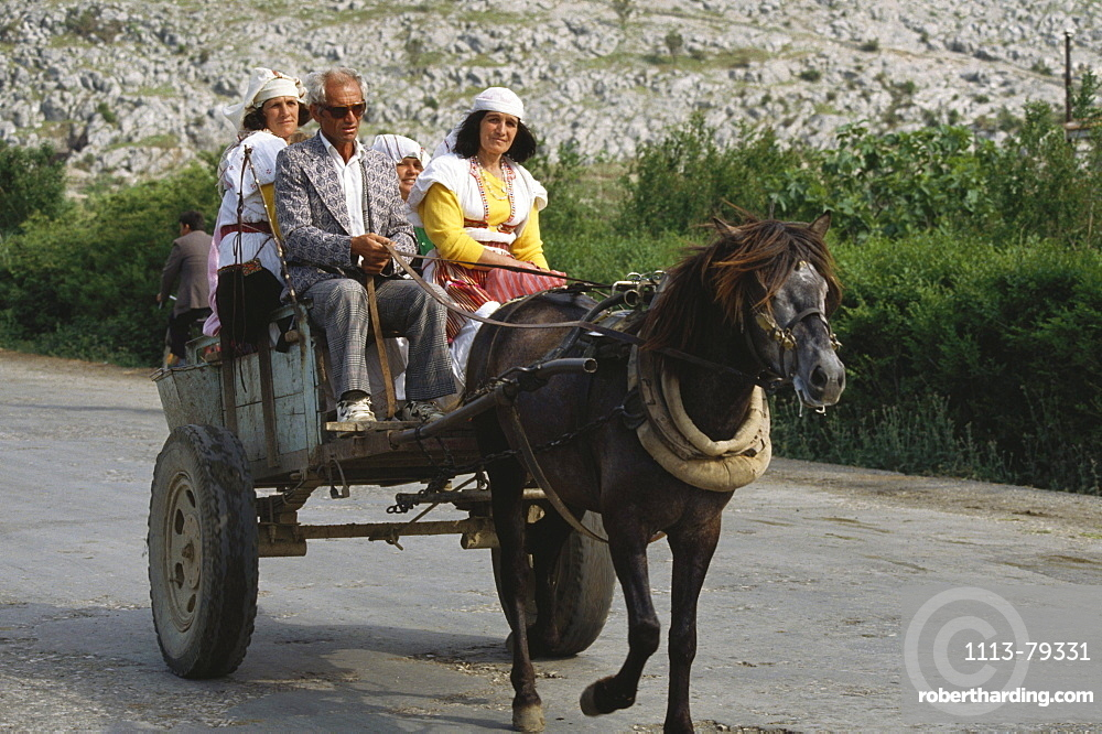 Locals in a horse carriage, landscape, North Albania
