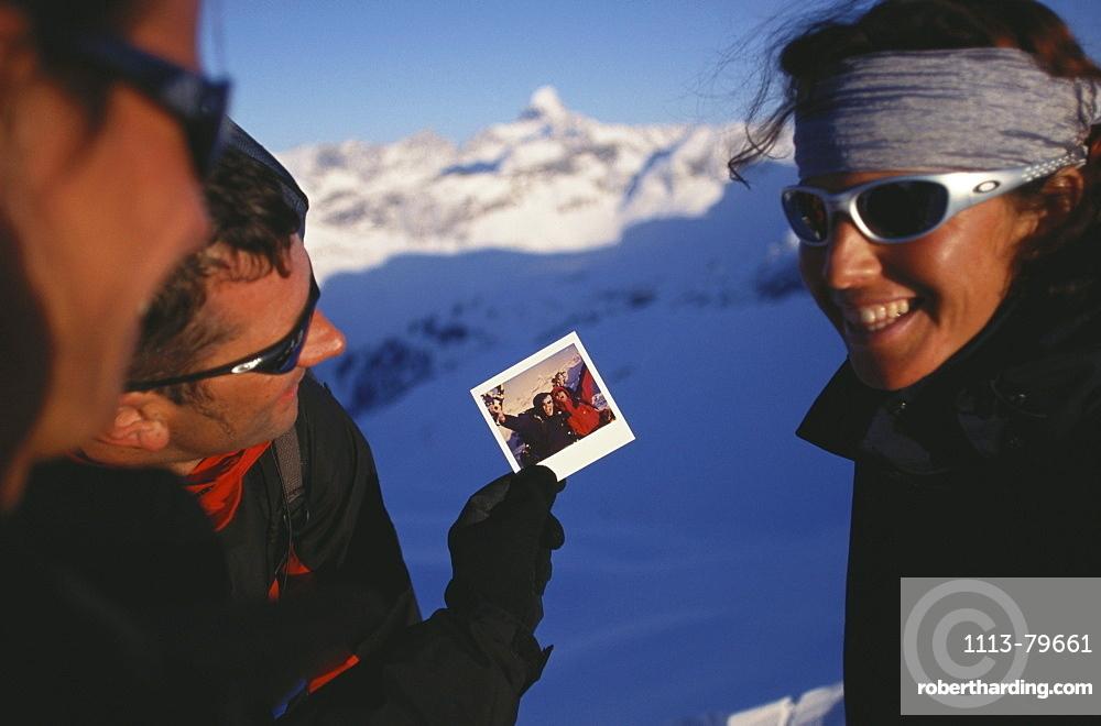 Man showing photograph to two friends, Snowshoeing, Mountain sports, Winter, Nebelhorn, Allgaeu, Bavaria, Germany