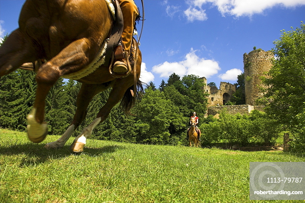 Two horseriders galloping over a field, Castle Brandegg ruins in the background, Muehlviertel, Upper Austria, Austria