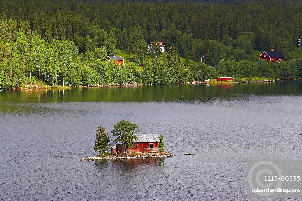 Small island with red wooden house in the lake Hetoegeln near Gaeddede, Jaemtland, northern Sweden