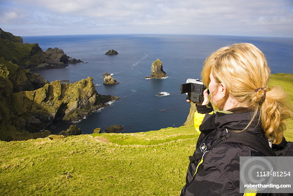 A woman filming the wild coast of Hermaness, Nature Protection Area, island of Unst, Shetland islands, Scotland, Great Britain, UK