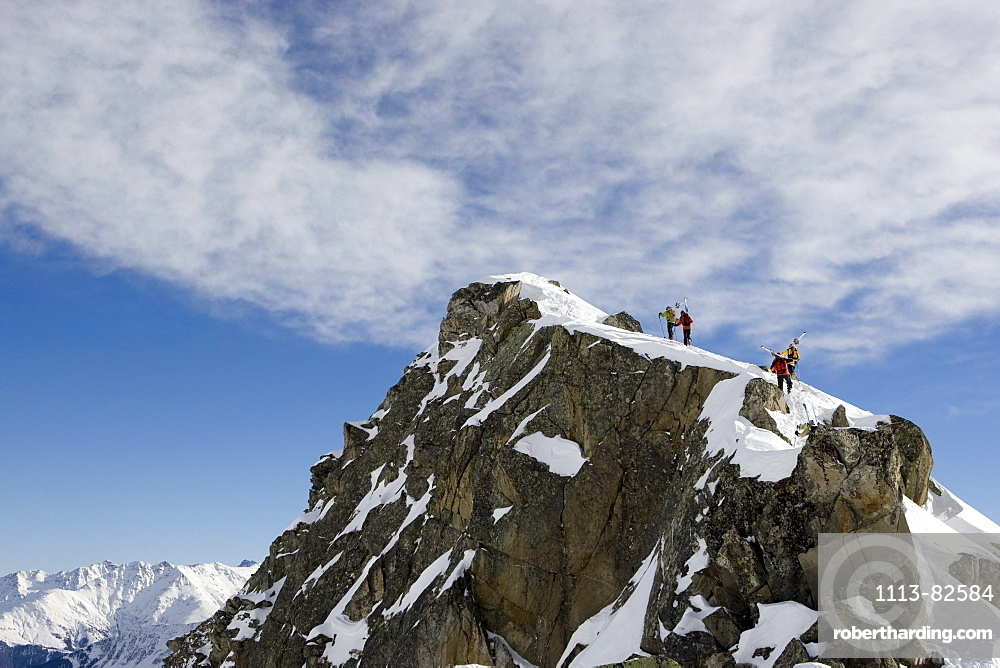 Group of freerider carrying skies on mount La Muota, Disentis, Grisons, Switzerland