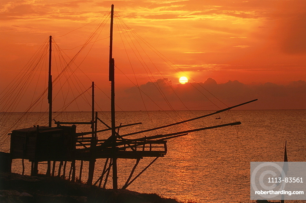Silouette of a fishing net frame at sunrise, Trabucco, Punta Lunga near Vieste, Gargano, Apulia, Italy