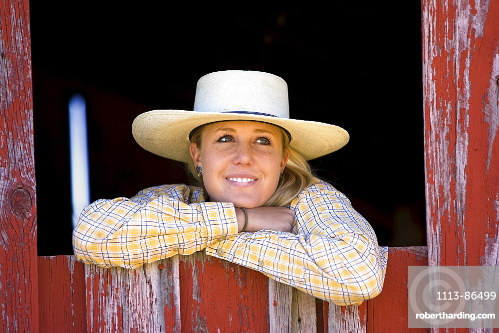 Cowgirl looking out of barn-window, wildwest, Oregon, USA