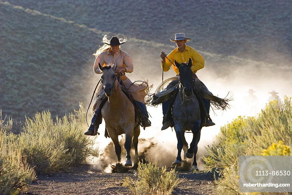 cowgirl and cowboy riding, Oregon, USA