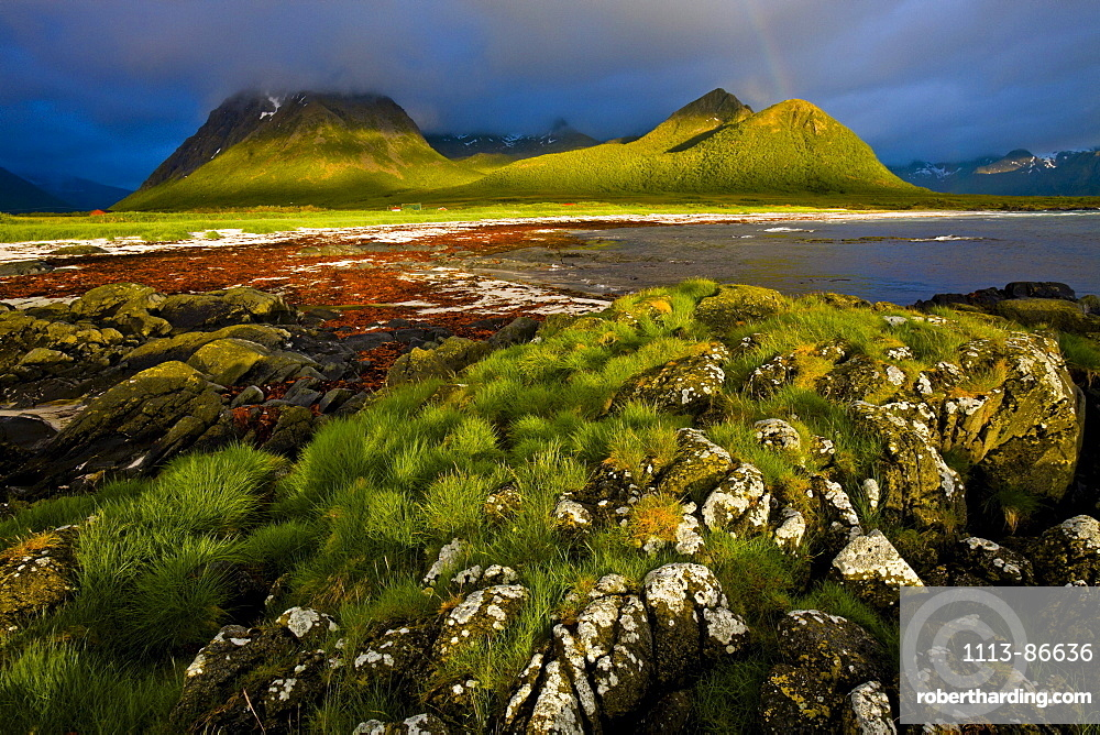 The midnight sun shines on the coastal mountains and beach, A rainbow is forming in the dark clouds, Hadselsand beach, Austvagoya Island, Lofoten, Norway