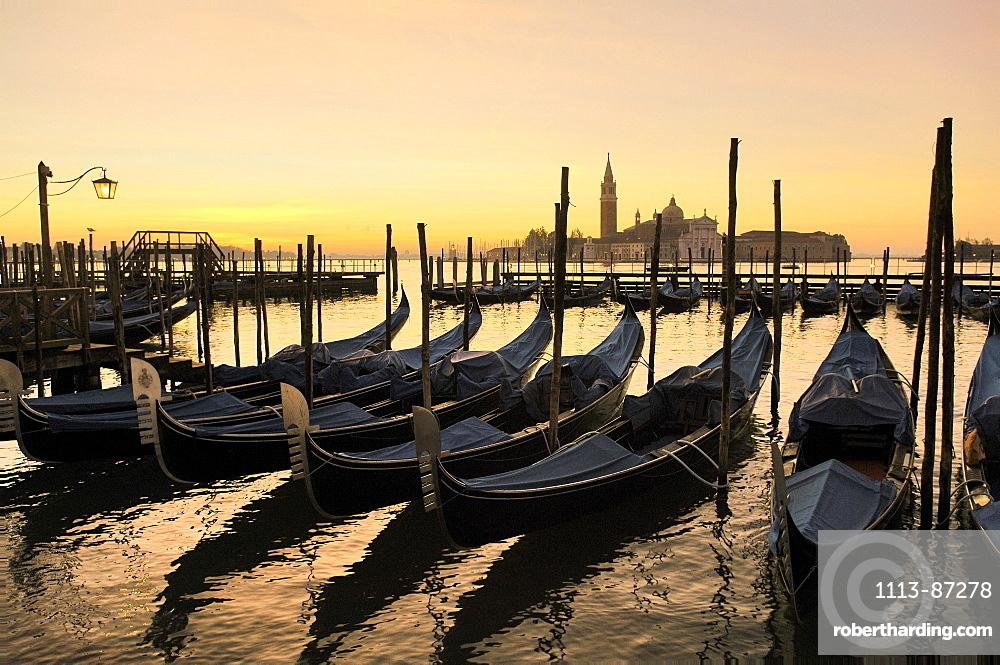 Gondola in a row and Isola San Giorgio in the background, Venice, Veneto, Italy