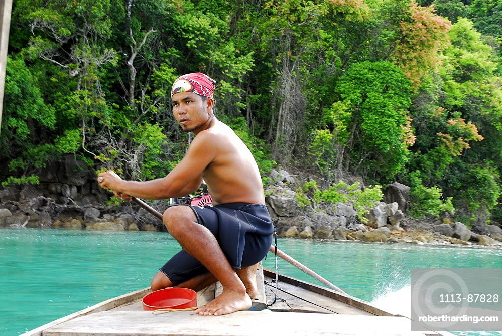 Local man steering a longtail boat, Surin Islands Marine National Park, Ko Surin, Phang Nga, Thailand