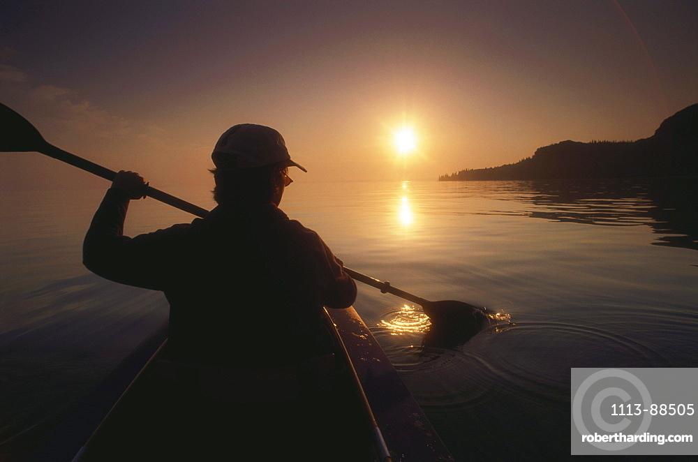 Young woman in a kayak paddling on Garda Lake at sunset, Verona province, Veneto, Italy