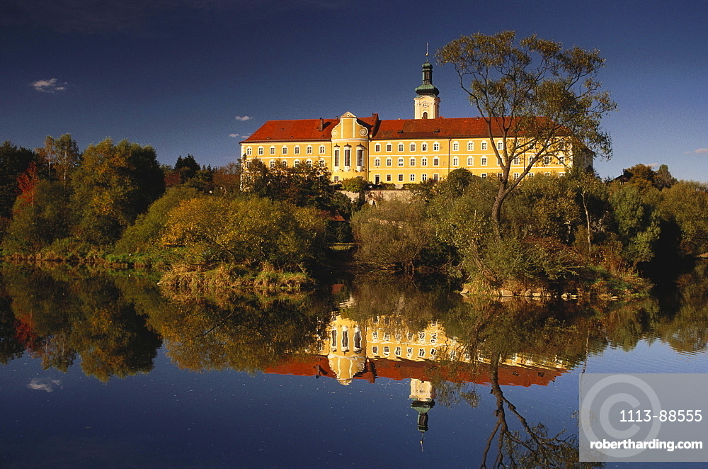 Calm waters of river Regen reflecting the former Cistercian abbey of Walderbach, Bavarian Forest, Upper Palatinate, Bavaria, Germany