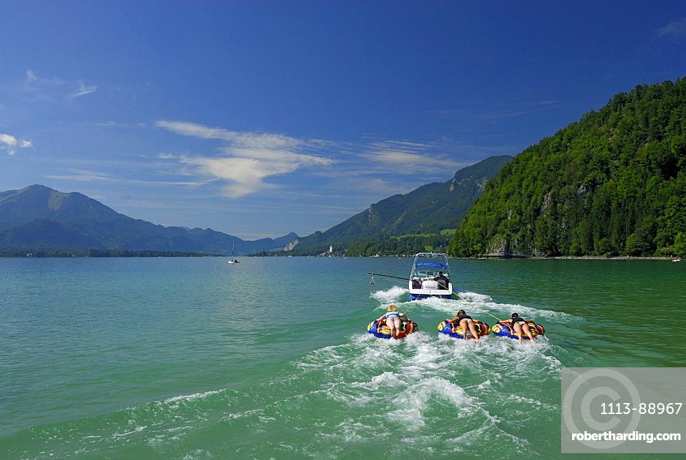 three young women tube riding behind motor boat, lake Abersee, lake Wolfgangsee, Salzkammergut, Salzburg, Austria