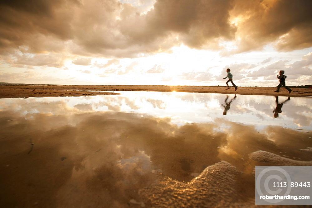 Two children running along the beach on a cloudy day, Reflection, Segeltorpstrandet, Halmstadt, Skane, Sweden