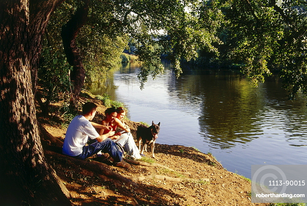 Three young people and a dog having a picnic near river, Witten, Ruhr Valley, Ruhr, Northrhine Westphalia, Germany