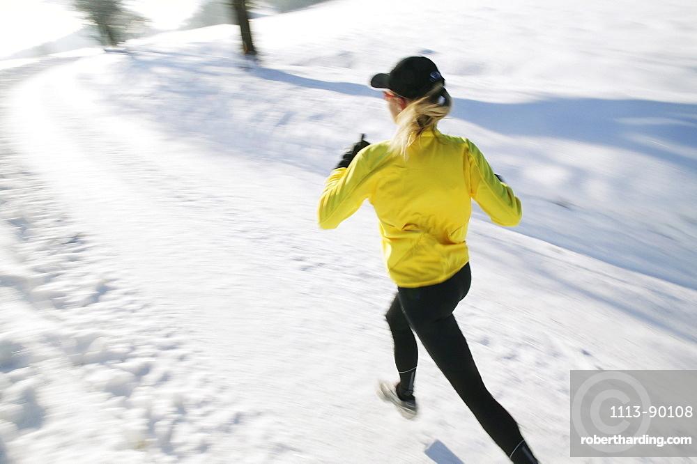 Woman jogging on snowy road, Styria, Austria