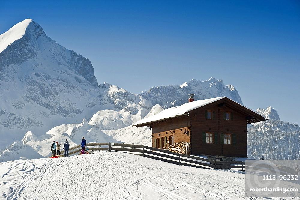 People sledging at Eckbauer, Alpspitze and Zugspitze in the background, Garmisch-Partenkirchen, Bavaria, Germany