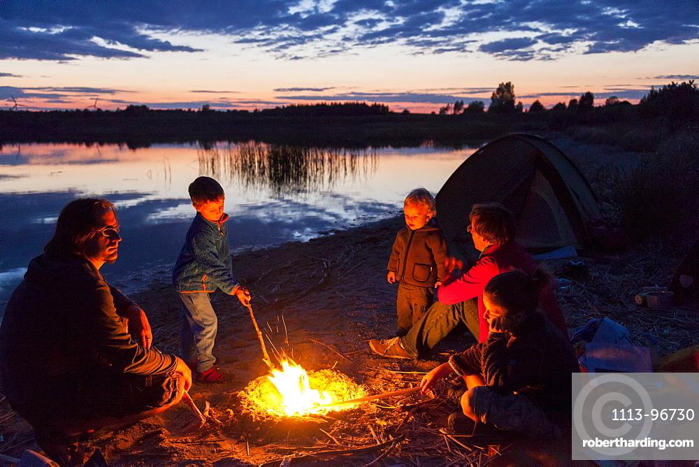 Family at campfire, Werbeliner See, Saxony, Germany