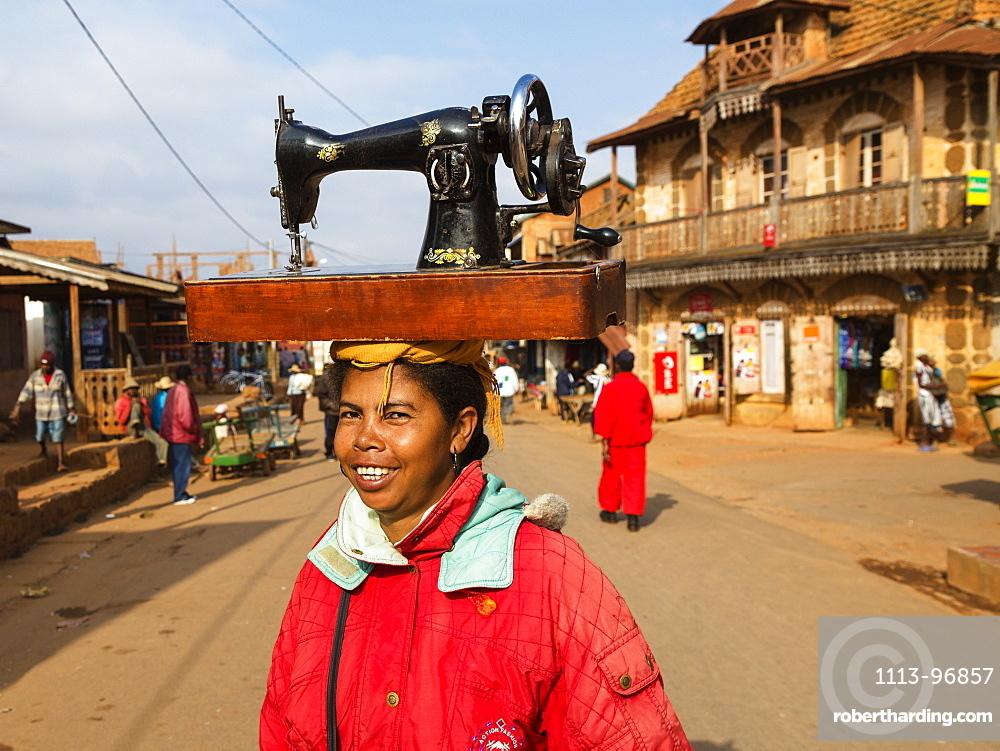 Madagascan woman carrying a sewing machine on her head, Betsileo tribe, Ambalavao, Fianarantsoa Region, Madagascar, Africa