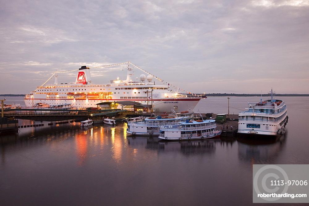 Cruise ship MS Deutschland (Reederei Peter Deilmann) and Amazon river boats at dusk, Manaus, Amazonas, Brazil