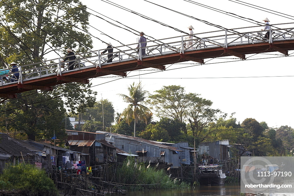Stilted houses and suspension bridge over Mekong canal, Long Xuyen, An Giang Province, Vietnam