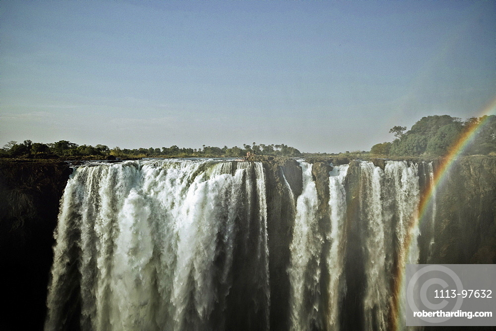 A group of people standing at the edge of Victoria Falls, Sambia, Africa