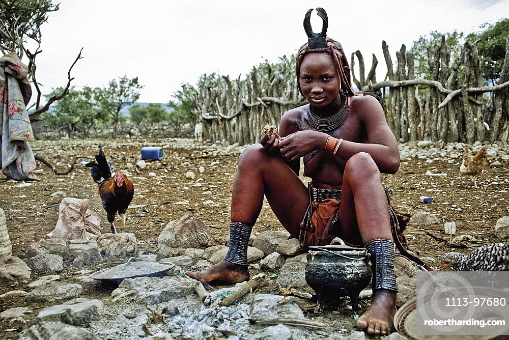 Woman of the Himba tribe sitting at the campfire, Kaokoland, Namibia, Africa