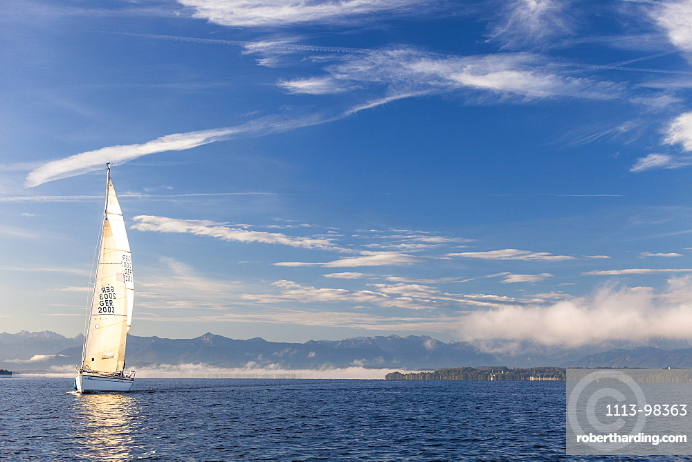 Sailing boat on Lake Starnberg, the Alps in background, Bavaria, Germany