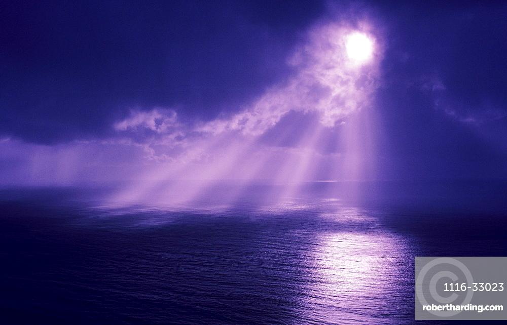 Sunlight bursting through dark clouds.