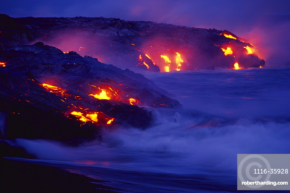 Hawaii, Big Island, Hawaii Volcanoes National Park, Lava flows into ocean at night, creating a purple mist.