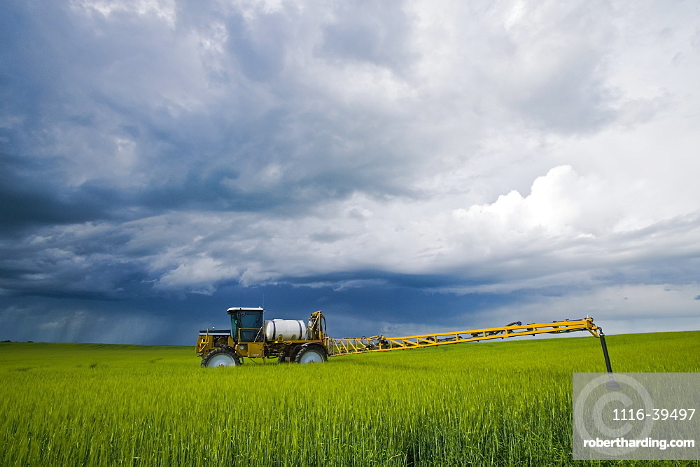 A high clearance sprayer that was applying fungicide on barley sits in a field as a storm approaches, near Holland, Manitoba, Canada