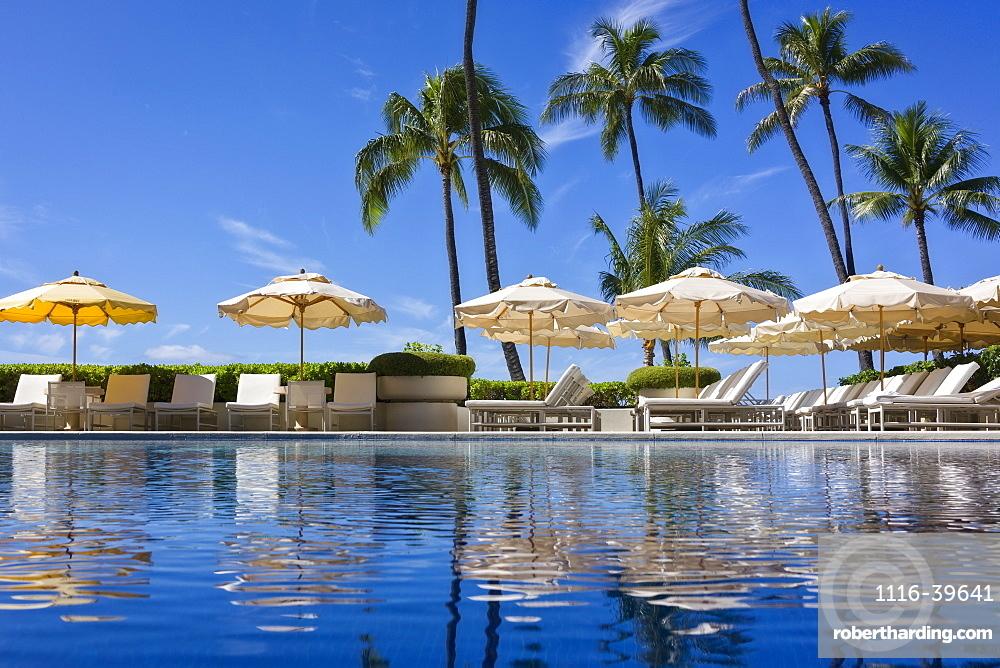 Halekalani Pool at Waikiki with palm trees and umbrellas reflected in the water, Waikiki, Oahu, Hawaii, United States of America