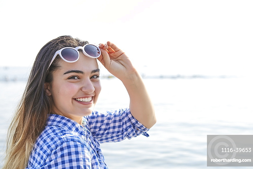 Portrait of a teenage girl at the water's edge at Woodbine Beach in summer, Toronto, Ontario, Canada