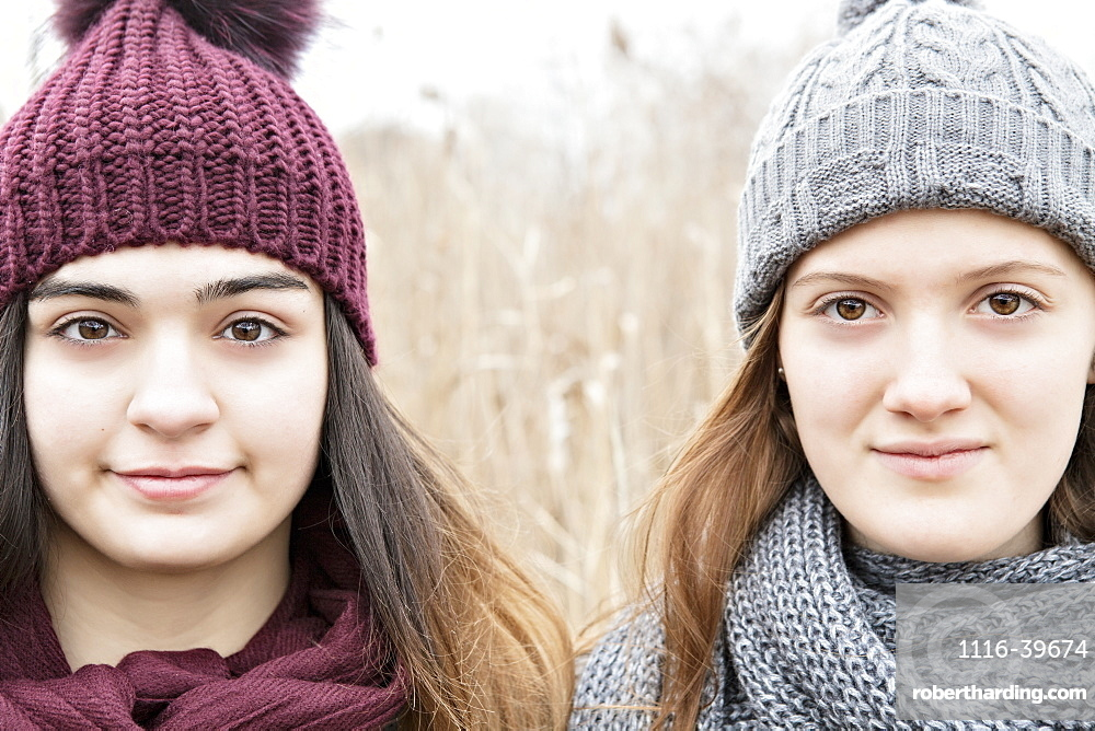 Two teenage girls wearing knit hats and scarves and looking at the camera, Scarborough, Ontario, Canada