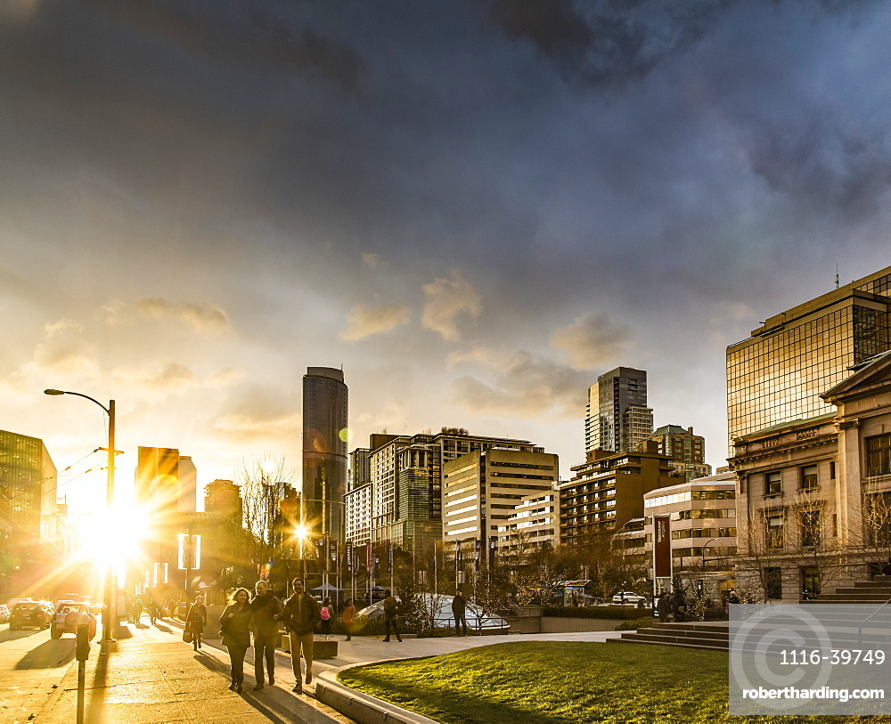 A street scene in Vancouver at sunset with pedestrians and buildings reflecting sunlight, Vancouver, British Columbia, Canada