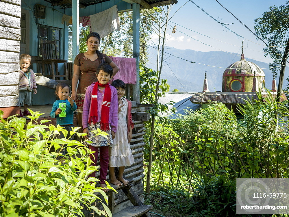 A mother with four children standing on the steps of their home near the Glenburn Tea Estate, West Bengal, India