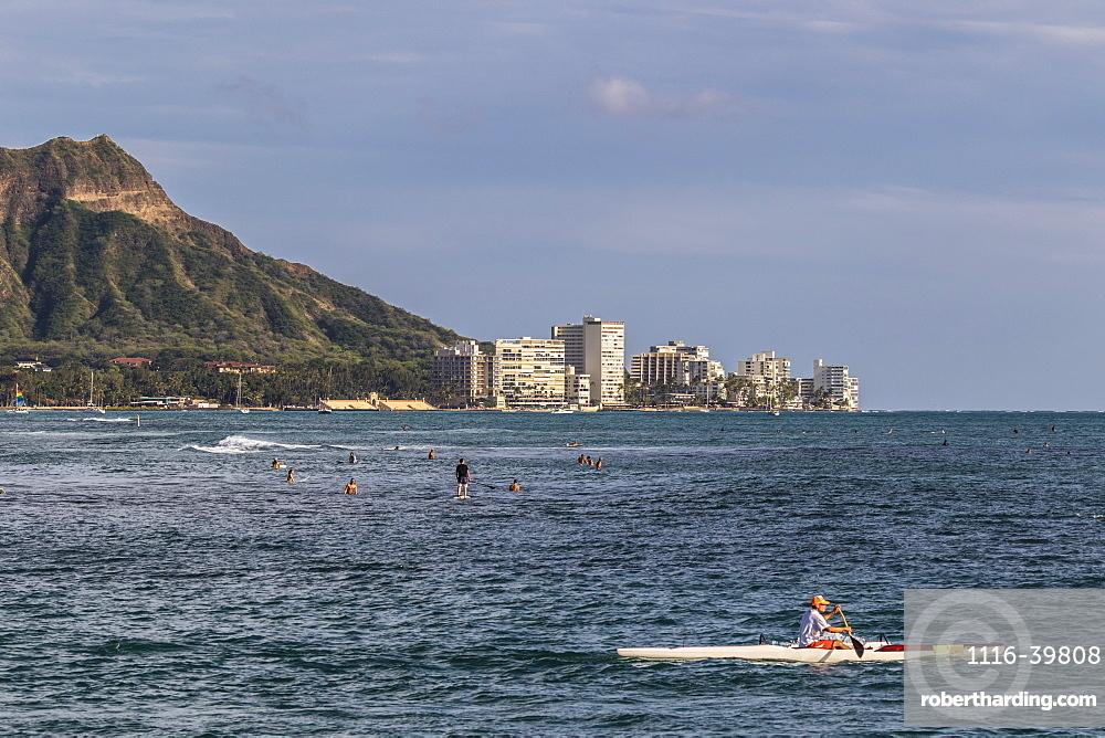 View of Diamond Head, Waikiki, and the two major Hawaiian watersports outrigger canoeing and surfing, from Magic Island, Ala Moana Beach Park, Honolulu, Hawaii, United States of America
