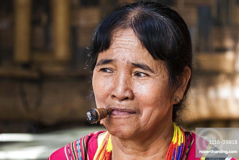 Lavae woman smoking a cigar in the ethnic village at Pha Suam, Bolaven Plateau, Champasak, Laos