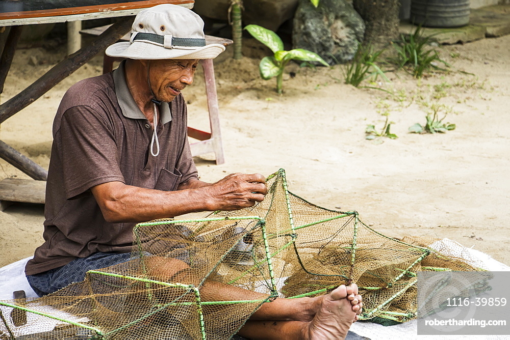 Fisherman sitting and repairing a net, Hoi An Ancient Town, Quang Nam, Vietnam