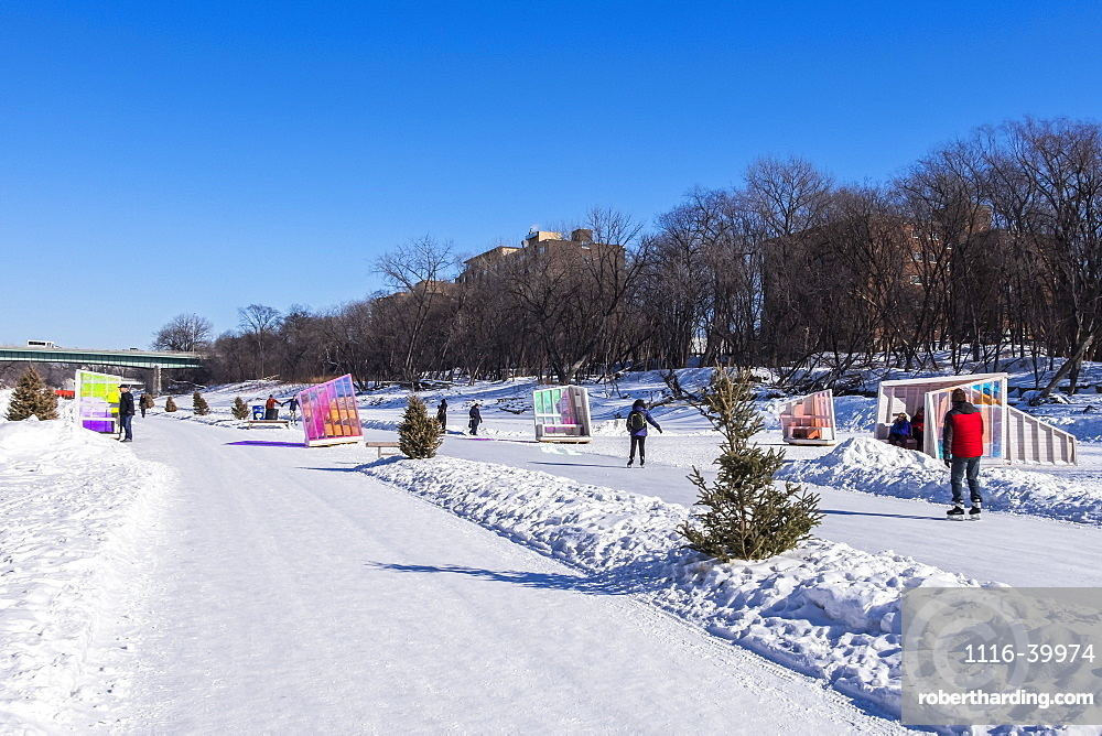 People walking and skating along the Red River Mutual Trail in Winnipeg, where artistic warming huts are on display, Winnipeg, Manitoba, Canada