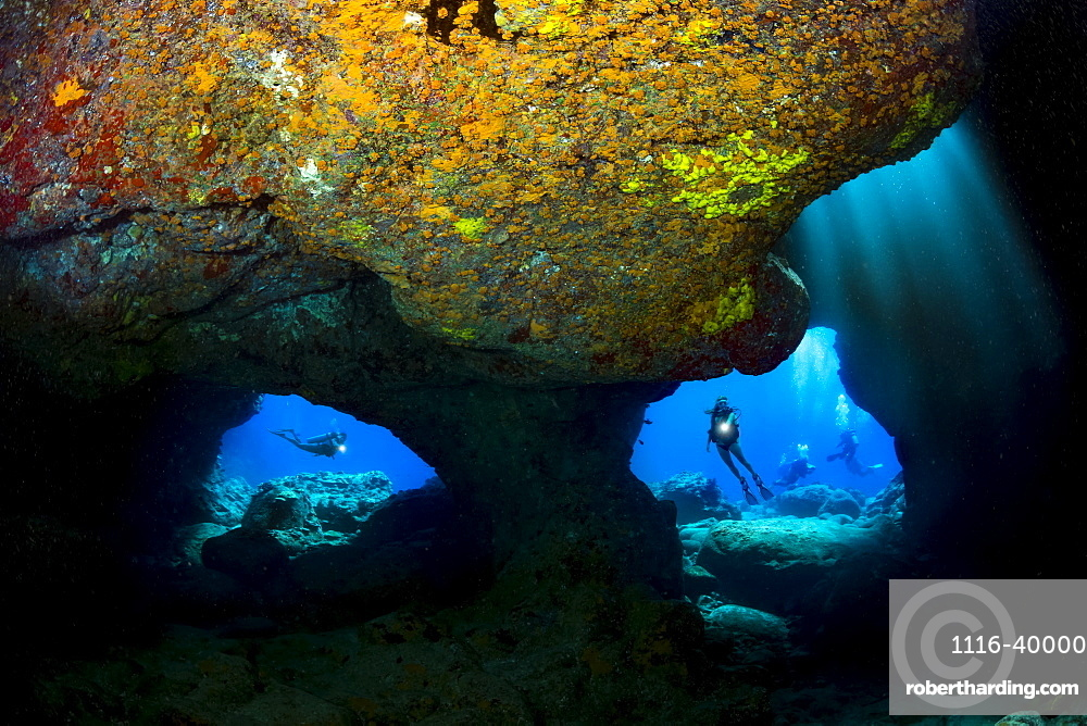 Divers are framed by the twin openings at a dive site known as Skull Cave off the Kona coast of the Big Island, Hawaii, United States of America