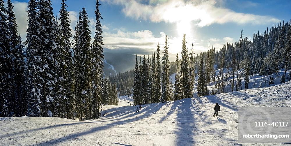 Skiers on a run at Sun Peaks ski resort, Kamloops, British Columbia, Canada