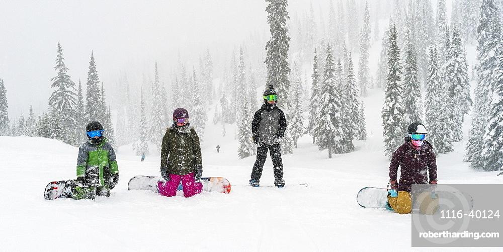 Snowboarders kneeling and resting at Sun Peaks Resort, Kamloops, British Columbia, Canada
