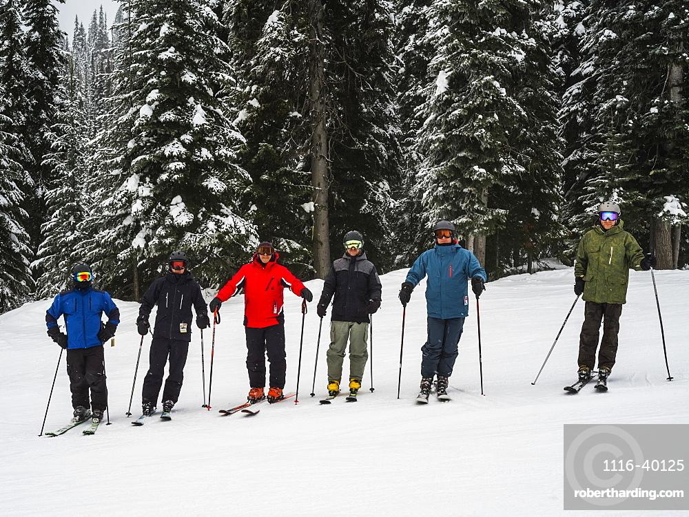 Skiers standing in a row, Sun Peaks Resort, Kamloops, British Columbia, Canada