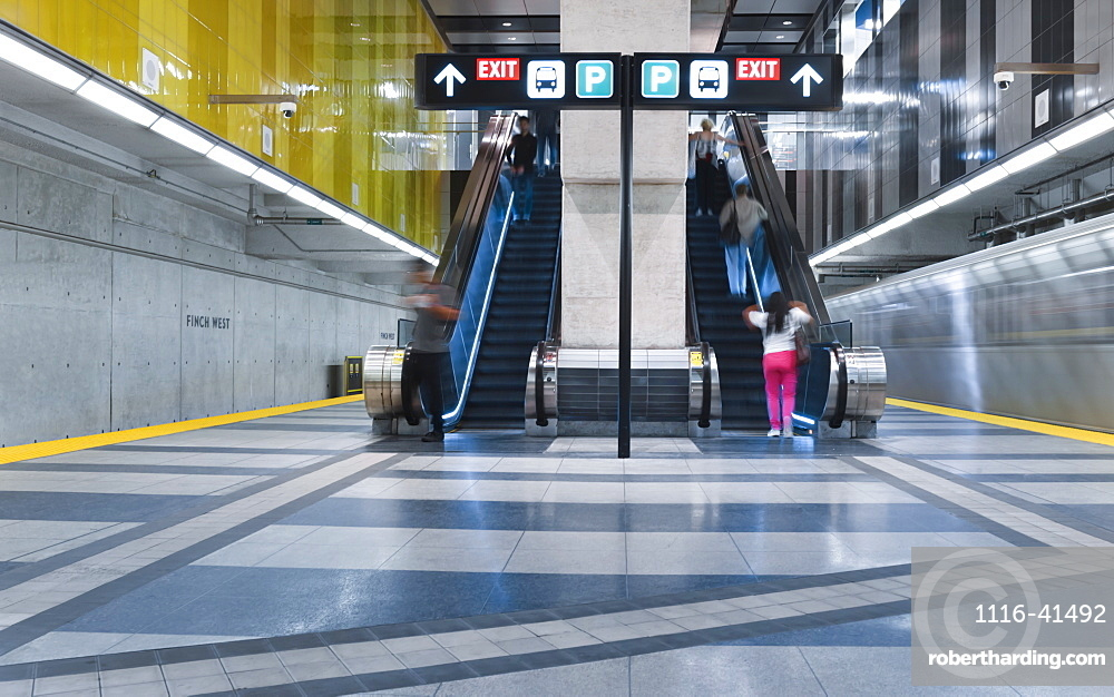 Interior train leaving the Finch West subway station on the Yonge-University line, passengers on an escalator, Toronto, Ontario, Canada