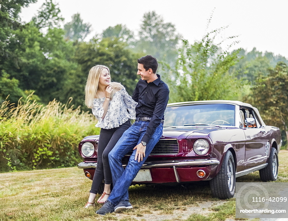 A young couple standing with a vintage sports car, Bothell, Washington, United States of America