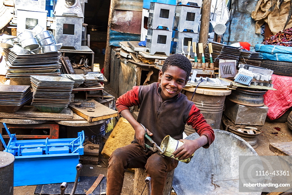 Eritrean boy cutting a can at the Medeber Market, where artisans recycle old tyres and tins to make new artifacts, Asmara, Central Region, Eritrea