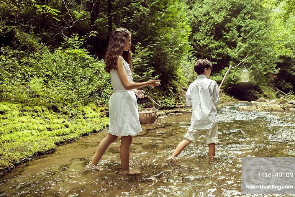 A girl and boy wading in a shallow river, the girl carrying a basket of flowers and the boy carrying a stick with a jar full of fireflies, Ontario, Canada