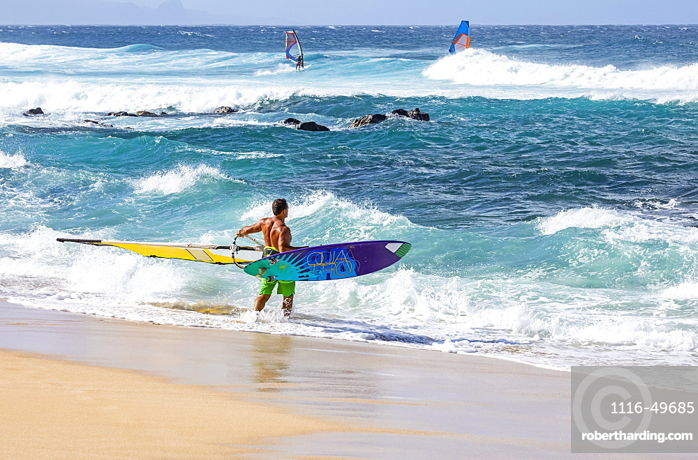 Three windsurfers, one standing on the beach at the water's edge looking out, Kihei, Maui, Hawaii, United States of America