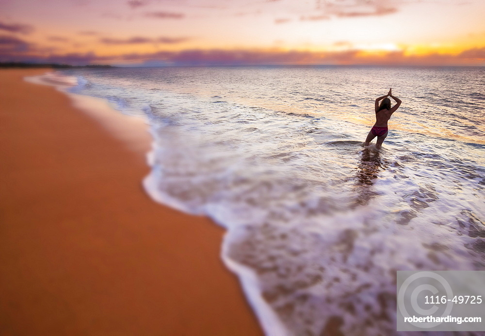 A blurred image of a woman standing in the surf, looking out at the sunset on the two mile long, three hundred feet wide, Papohaku Beach on the west shore of Molokai. This is the longest white-sand beach in the Hawaiian Islands, Molokai, Hawaii, United States of America