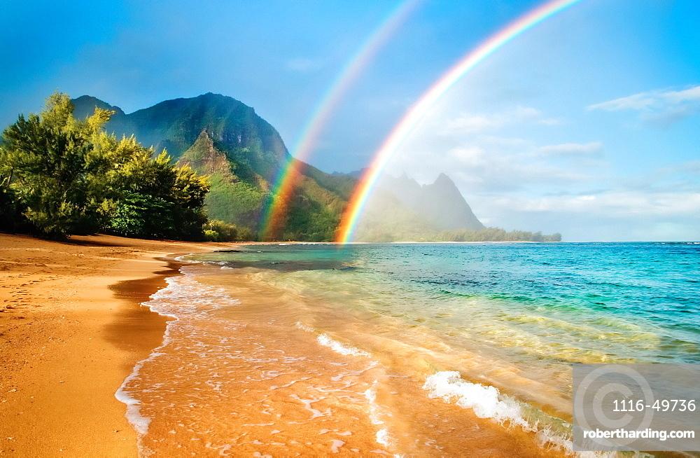 A double rainbow over the coastline of a Hawaiian island with mountains and turquoise water, Haena, Kauai, Hawaii, United States of America