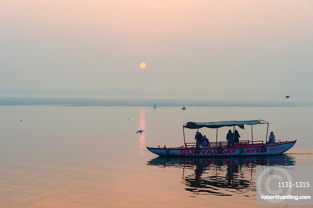 Small boats on Ganges River at sunset, Varanasi, Uttar Pradesh, India